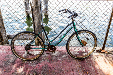 rusty fence: old rotten bike at a rusty fence at the canal in Miami