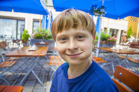 freising: cute smiling child eats and has joy in the outdoor restaurant