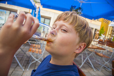 freising: boy enjoys drinking in the outdoor restaurant from a big glass