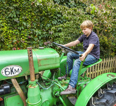 old tractor: young boy playing with an old tractor