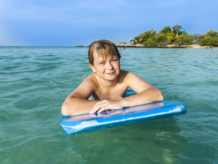 boy is swimming on his surfboard in  a beautiful sea with crystal clear water and blue sky photo