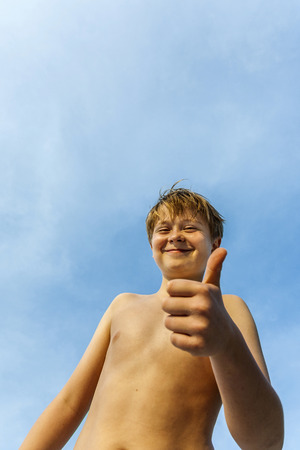 allright: happy smiling young boy with background blue sky gives fingersign all-right, thumbs-up