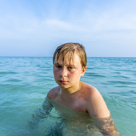 angry sad young boy in the beautiful ocean with sunburn