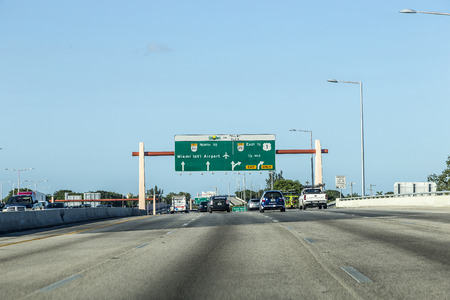 toll: MIAMI, USA - AUG 27, 2014: driving the Miami Highway from the airport direction East in Miami, USA. Sunpass lane on left hand side is for toll only. Editorial