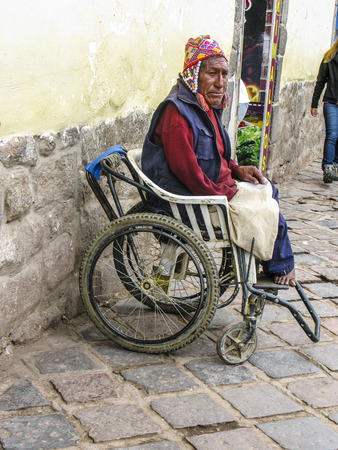 begs: CUZCO, PERU - JAN 18, 2015: handicapped man sits in an wheelchair and begs for an alm  in Cuzco, Peru. Editorial