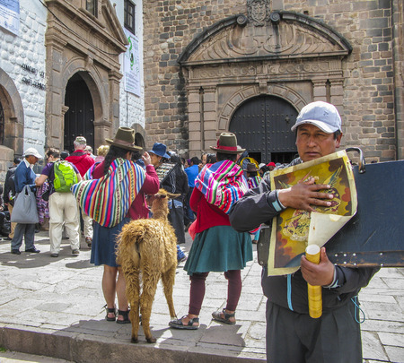 indios: CUSZO, PERU - JAN 16, 2015: indian woman pose with a lama for tourists in Cuzco, Peru to earn some money. An indio man sells paintings.
