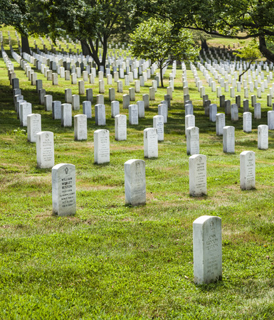 ARLINGTON, USA - JUL 15, 2010: Gravestones on Arlington National Cemetery  in Arlington, USA. Headstones mark soldier graves who died in every conflict from Revolution to Sept 11.