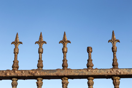 guard rail: Decorative old rusty steel Gate against blue sky Stock Photo