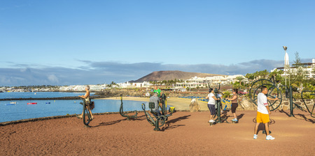 playa blanca: PLAYA BLANCA, SPAIN - NOV 12, 2014: people train at the outdoor fitness station in Playa Blanca, Spain. The public fitness spot opened in 2009 and is sponsored by La caja de Canarias.