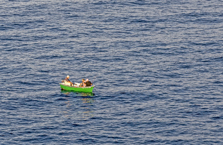 outboard: PLAYA BLANCA, SPAIN  - NOV 18, 2014: fishermen in a small boat in the morning go for a catch in Playa Blanca, Spain. Most former fishermen work in tourist sector in Lanzarote nowadays. Editorial
