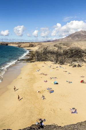 playa blanca: PLAYA BLANCA, SPAIN - NOV 18, 2014: Many tourists enjoy Papagayo beach on a sunny  day in Playa Blanca, Spain. The beaches belong to a protected nature area.