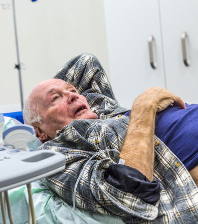 Sick senior lying in a hospital bed with iv drip attached on his hand Stock Photo