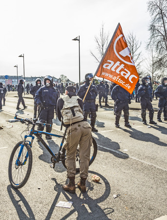 attac: FRANKFURT, GERMANY - MAR 18, 2015: people demonstrate against EZB and Capitalism in Frankfurt, Germany. Man shows attac banner.