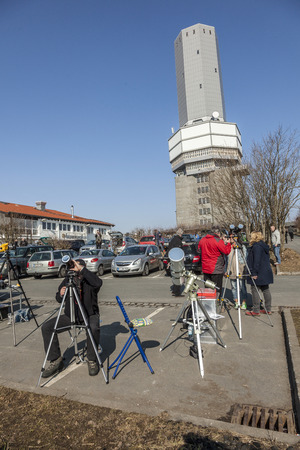 SCHMITTEN, GERMANY - MAR 20, 2014: radio and TV station at Mount Grosser Feldberg  in Schmitten, Germany. People watch the partial eclipse.