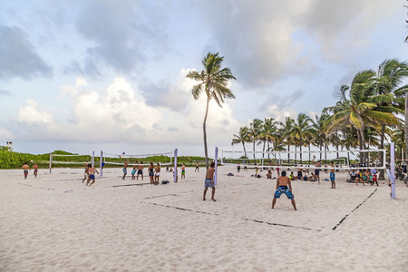 south beach: MIAMI, USA - Aug 30, 2014: people enjoy playing volleyball in Miami, USA. South beach is famous for the public sports areas  used mainly in late afternoon till dawn.