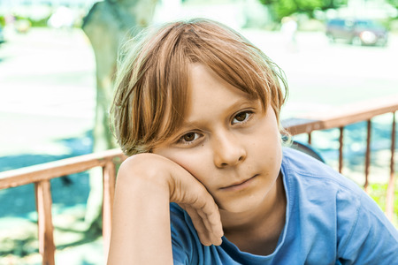 unsatisfied: boy with brown hair is looking displeased Stock Photo