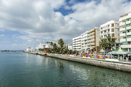 enables: ARRECIFE, SPAIN - NOV 17, 2014: people walk along the promenade in Arrecife, Spain. The modern promenade was restored in 2008 and enables a relaxed walk for people along the scenic ocean and the harbor. Editorial