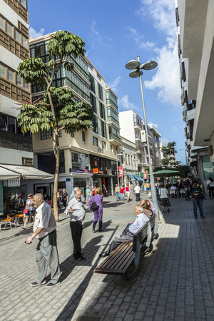 enables: ARRECIFE, SPAIN - NOV 17, 2014: people walk along the pedestrian zone in Arrecife, Spain. The modern shopping street is closed for cars and enables a relaxing downtown shopping.