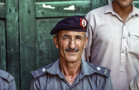 proudly: PESHAWAR, PAKISTAN - JUNE 30, 1987: portrait of proud elderly policeman in Peshawar, Pakistan. He likes to pose for tourists and tells proudly about the british history. Editorial