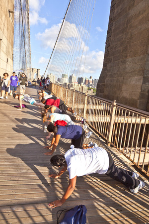 pushup: NEW YORK, USA - JULY 9, 2010: people exercise push-up at Brooklyn bridge in New York, USA. Brooklyn Bridge was constructed under Roeblings 1840 patent for the in-situ spinning of wire rope.