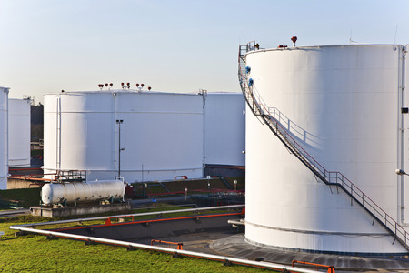 white tanks in tank farm with blue clear sky Stock Photo