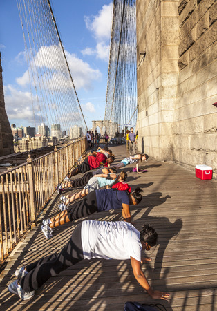 NEW YORK, USA - JULY 7, 2010: people exercise push-up at Brooklyn bridge in late afternoon in New York, USA. Brooklyn Bridge was constructed under Roeblings 1840 patent for the in-situ spinning of wire rope.