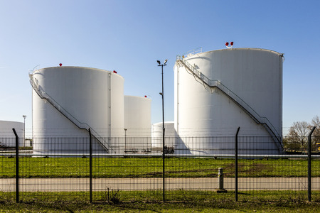 farm structure: white tanks in tank farm with iron staircase under blue sky