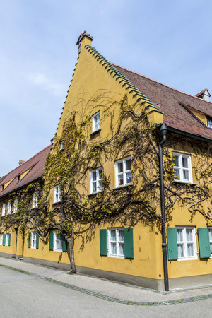 residential settlement: AUGSBURG, GERMANY - APRIL 29, 2015: The Fuggerei is the worlds oldest social housing complex still in use in Augsburg, Germany.