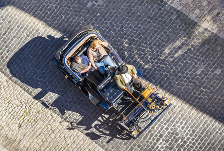 19 year old: ROTHENBURG, GERMANY - APR 19, 2015: guide waits for tourists with an old vintage car in Rothenburg, Germany. The medieval town attracts over 2 million visitors every year.
