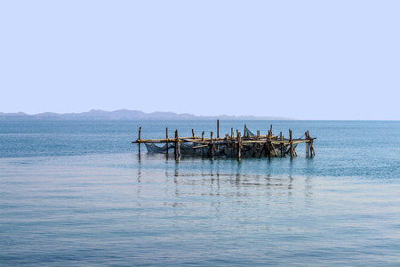 fishing industries: fishing net at an artifical bamboo island in the ocean