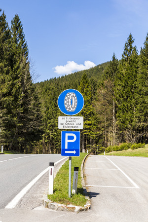 snow tire: snow chain sign with parking place to change in the alps Stock Photo