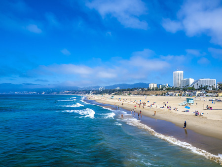 LOS ANGELES, USA - SEP 23, 2014: Many people sunbath on the sand beach and swim in the ocean in Santa Monica Beach, Los Angeles, CA, USA 報道画像