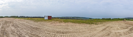 skidmark: panoramic view of an area on a hill with tracks of digger and a container