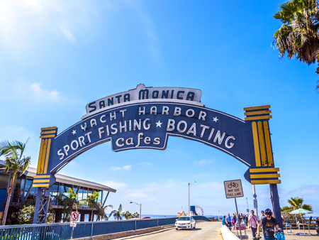 wooden dock: SANTA MONICA, USA - SEP 23, 2014: The welcoming arch of Santa Monica Pier in Santa Monica, USA. The site is an iconic 100-year-old landmark for California visitors.
