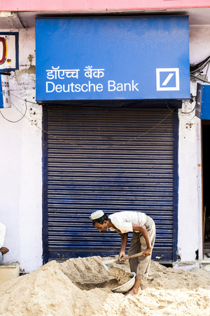 jaipur: JAIPUR, INDIA - OCT 19, 2010: worker at a construction site carries sand in front of a closed bank building from germany Bank in Jaipur, India. Editorial