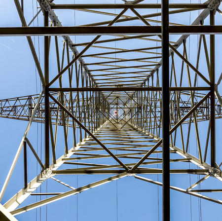 energy needs: A high voltage electricity pylons against blue sky and cloud
