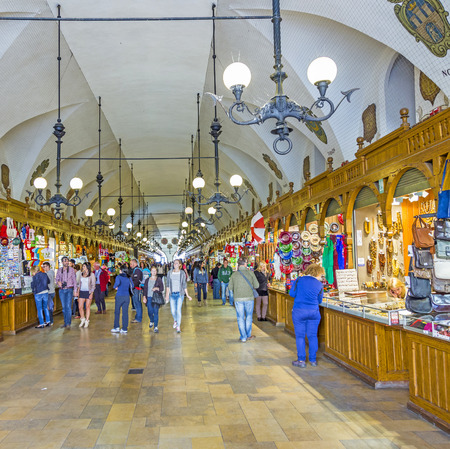KRAKOW, POLAND - OCT 7, 2014: people shopping inside Sukiennice - medieval trade area (The Cloth Hall ) in Krakow, Poland.It was once a major centre of international trade.