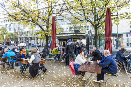 renamed: BERLIN, GERMANY - OCT 27, 2014: old vintage Kiosk name is renamed to oval office and people enjoy on tables the autumn summer in Berlin, Germany.