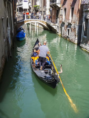 permissions: VENICE, ITALY - SEP 13, 2014: Venetian gondolas with tourist sail in the canal in Venice. Permissions for gondolas are very expensive and limited.