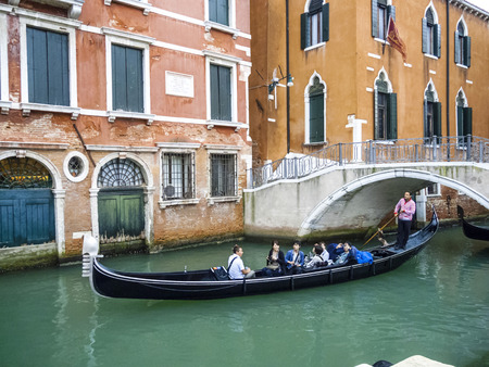 permissions: VENICE, ITALY - SEP 12, 2014: Venetian gondolas with tourist sail in the canal in Venice. Permissions for gondolas are very expensive and limited. Editorial