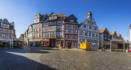 the existing: BUTZBACH, GERMANY - JUNE 4, 2015: people enjoy the beautiful medieval market place in Butzbach, Germany. In 143 the market place was build with cobble stones and the still existing fountain.