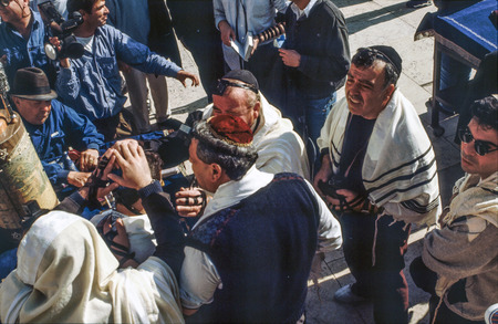 annexation: JERUSALEM - JAN 1 1994: Orthodox jewish men pray at the Western Wall in Jerusalem, Israel. Israels annexation of East Jerusalem in 1967, including the Old City, was never internationally recognized.
