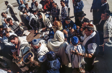 JERUSALEM - JAN 1 1994: Orthodox jewish men pray at the Western Wall in Jerusalem, Israel. Israels annexation of East Jerusalem in 1967, including the Old City, was never internationally recognized.