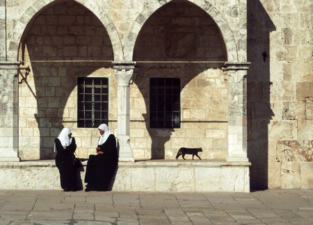 told: JERUSALEM, ISRAEL - JAN 1, 1994: arab women sit at the wall of the temple area in Jerusalem. Jerusalem is a holy city to the three major Abrahamic religions - Judaism, Christianity and Islam. Editorial