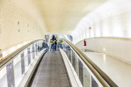 long handled: PARIS, FRANCE - JUNE 13, 2014: long moving staircases in Terminal 1 at airport Charles de Gaulle in Paris, France. In 2013, the airport handled 62,052,917 passengers.