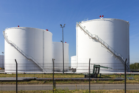 white tanks in tank farm with iron staircase under blue sky