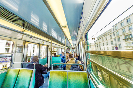 annually: PARIS , FRANCE- JUNE 10, 2015: Tourists and locals on a subway train in Paris, France. More than 30 million people visit Paris annually.