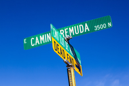 street names on green signs under blue sky in Tuscon, USA