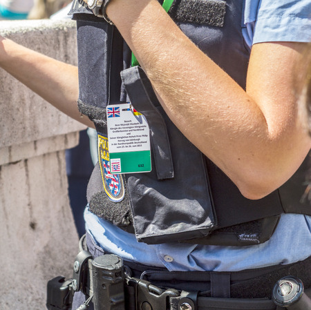 queen elizabeth: FRANKFURT, GERMANY - JUNE 26, 2015: police woman pays attention for the visit of queen Elizabeth II at the Roemer market square in Frankfurt, Germany. Sshe weares a special id card for identification. Editorial