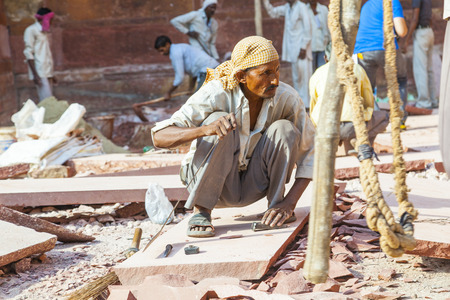 stone cutter: AGRA, INDIA - OCT 17, 2012: worker prepares sandstones for renovation of the Red Fort in Agra, India. The fort was mentioned for the first time in 1080 AD when a Ghaznavide force captured it. Editorial